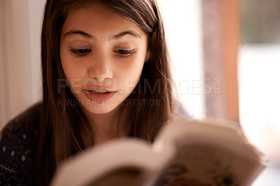 Buy stock photo Shot of a little girl reading a book at home