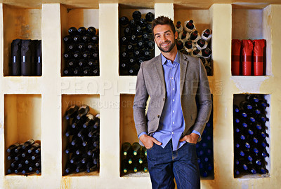 Buy stock photo A young man standing in front of a rack full of wine