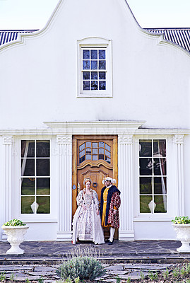 Buy stock photo Shot of a royal couple standing in front of their home