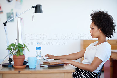 Buy stock photo Shot of an attractive young woman sitting at her workstation in the office. The commercial designs displayed in this image represent a simulation of a real product and have been changed or altered enough by our team of retouching and design specialists so that they are free of any copyright infringements