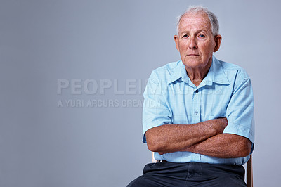 Buy stock photo Studio portrait of an elderly man with his arms crossed against a blue background