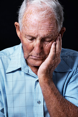 Buy stock photo Studio shot of a sad-looking elderly man with his hand on his chin isolated on black