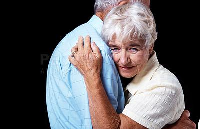 Buy stock photo Studio shot of an elderly couple hugging isolated on black