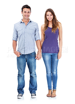 Buy stock photo Studio shot of a casual couple smiling at the camera and holding hands