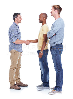 Buy stock photo Three male coworkers standing isolated on white as two men shake hands