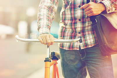 Buy stock photo Cropped shot of a man pushing his bicycle in the city