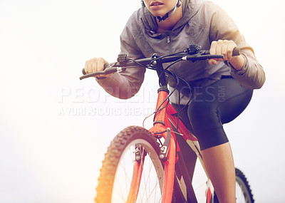 Buy stock photo Cropped shot of a female mountain biker out for an early morning ride