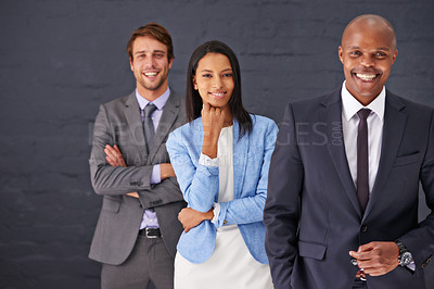 Buy stock photo Portrait of three businesspeople standing against a gray background