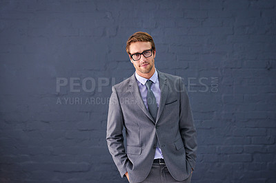 Buy stock photo Portrait of a handsome young businessman standing against a gray background