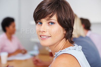 Buy stock photo Attractive young woman with people discussing in background