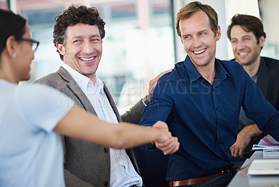 Buy stock photo Cropped shot of two business people shaking hands while sitting at a table