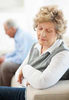 Buy stock photo A senior woman sitting on the opposite end of a sofa from her husband after an argument