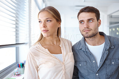 Buy stock photo Shot of two young office workers looking out of a window