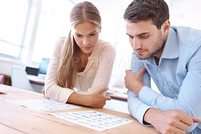Buy stock photo Shot of two young design professionals sitting at a table and editing photographs