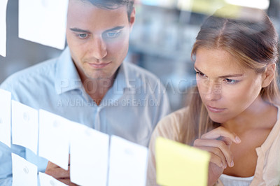 Buy stock photo Through the glass shot of two young businesspeople looking at sticky notes on a glass wall