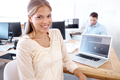 Buy stock photo Lovely young businesswoman sitting at her desk with her co-worker in the background - copyspace