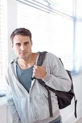 Buy stock photo Handsome young student standing with a backpack slung over his shouder - portrait