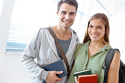 Buy stock photo Young student couple with their arms around each other holding books and smiling at the camera - portrait