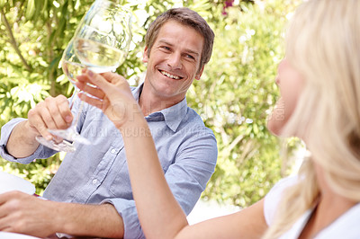 Buy stock photo A mature couple toasting their wine while out on a lunch date together