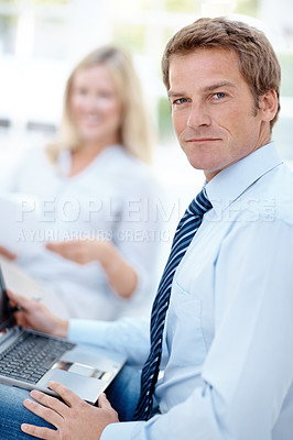 Buy stock photo A handsome man working on his laptop with a woman holding documents in the background