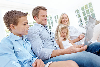 Buy stock photo A happy family looking at a laptop