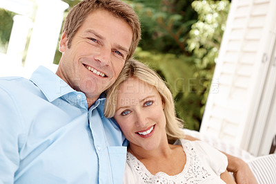 Buy stock photo Portrait of a smiling couple who are sitting outside in the sunshine