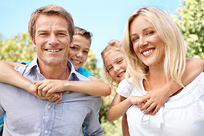 Buy stock photo Happy parents piggybacking their cute children while outdoors