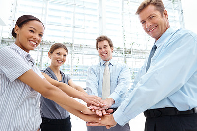Buy stock photo A smiling team of businesspeople putting their hands together in a show of team spirit