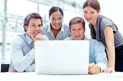 Buy stock photo A group of businesspeople working together on a laptop in their office