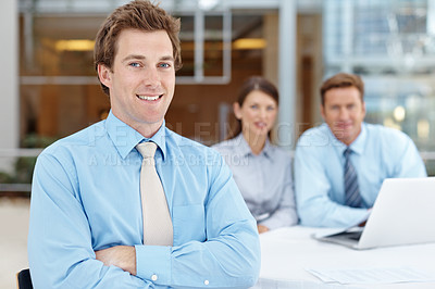 Buy stock photo Closeup of a young businessman smiling at the camera with his colleagues in the background