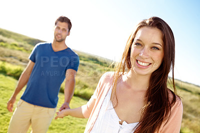 Buy stock photo A happy couple holding hands and walking in a field