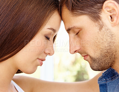 Buy stock photo Cropped close up shot of a young couple with their foreheads touching and their eyes closed