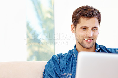 Buy stock photo Cropped shot of a handsome young man sitting on a sofa working on a laptop