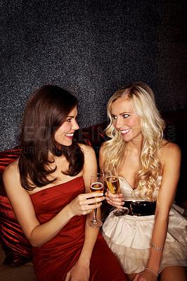 Buy stock photo Two beautiful women toasting in a nightclub