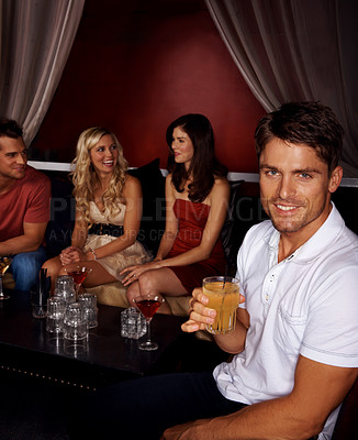 Buy stock photo Portrait of an handsome young man drinking a cocktail with his friends sitting behind him