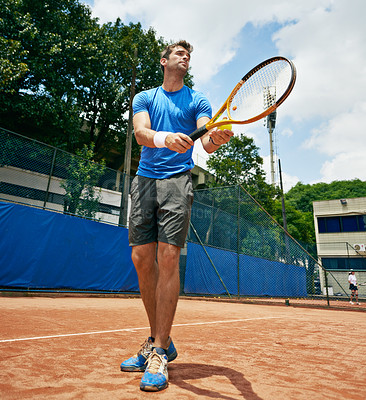 Buy stock photo Low angle shot of a tennis player serving