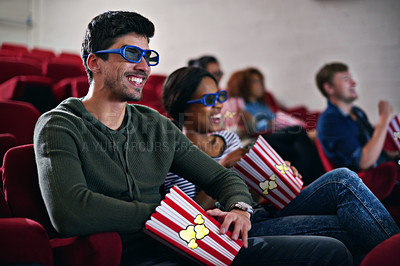 Buy stock photo Shot of a man smiling while watching a 3D movie at the cinema