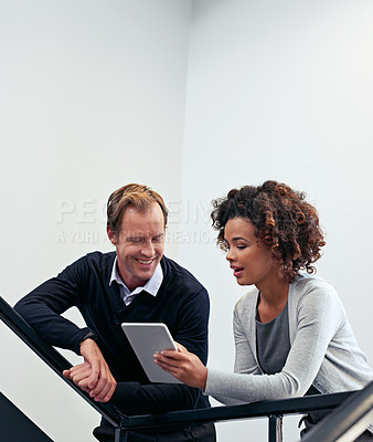 Buy stock photo Shot of two colleagues using a digital tablet while standing in a stairwell