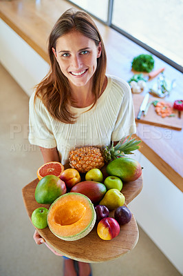 Buy stock photo Shot of an attractive young woman holding a cutting board full of fresh furit