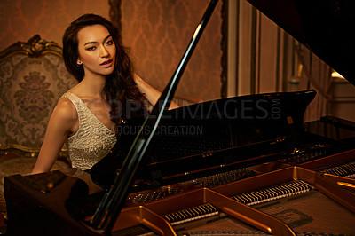 Buy stock photo Shot of a beautiful young woman playing the piano