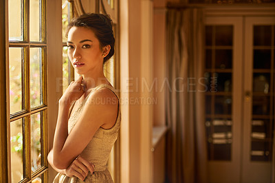 Buy stock photo Portrait of a beautiful young woman standing in an elegant room