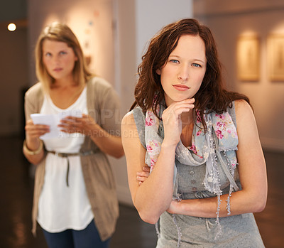 Buy stock photo Shot of two young women looking at paintings in a gallery