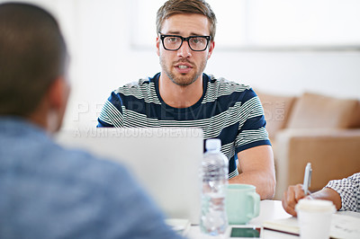 Buy stock photo Shot of a group of young designers working around a table