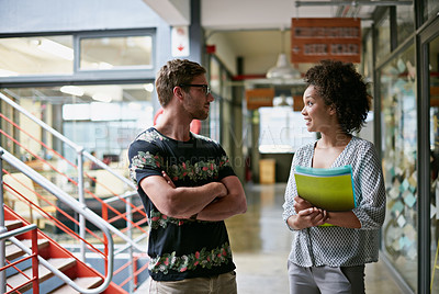 Buy stock photo Two colleagues talking to each other while walking