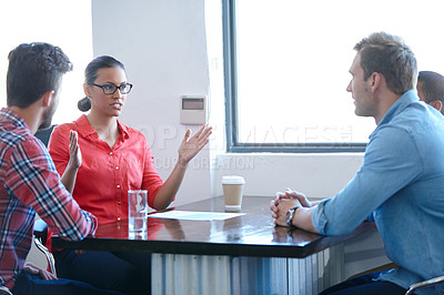 Buy stock photo Shot of of a female designer sharing her ideas with her colleagues in a meeting