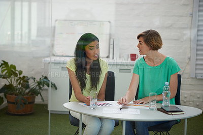 Buy stock photo Shot of two colleagues having a brainstorming meeting together