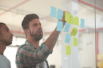 Buy stock photo Shot of two colleagues discussing ideas together on sticky notes