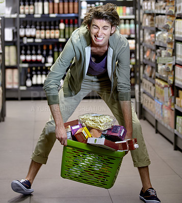 Buy stock photo A young man struggling to pick up his basket full of groceries