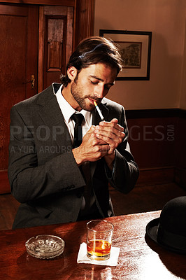 Buy stock photo Portrait of a well-dressed young man sitting at a bar with a drink and a smoke
