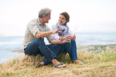 Buy stock photo Shot of a mature couple sitting in nature having a chat